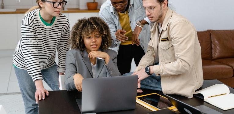 Man in brown jacket holding black laptop