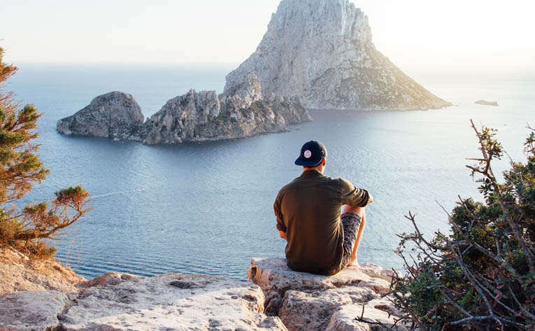 Man sitting by a cliff looking at the sea