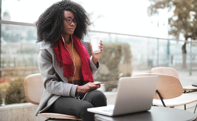 Woman drinking coffee with her laptop